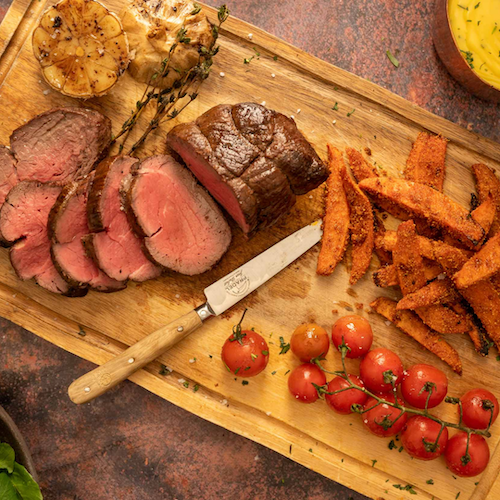 steak chateaubriand with sweet potato chips and tomatoes on a board