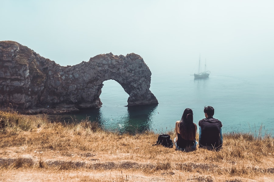 Couple sat overlooking sea with boat in the background.